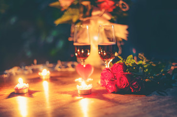 Valentines dinner romantic love concept Romantic table setting decorated with Red heart and couple champagne glass roses flower with candlelight