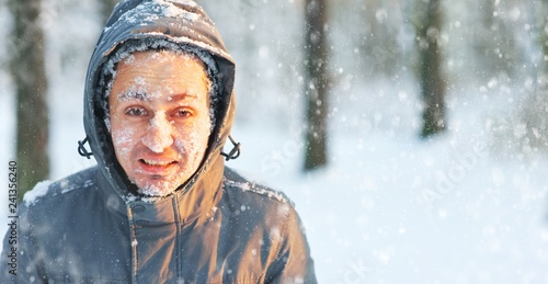 Frozen young man in a jacket with a hood covered with snow in winter forest Fototapeta