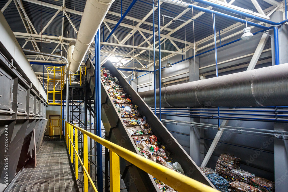 Fototapeta moving conveyor transporter on Modern waste recycling processing plant. Separate and sorting garbage collection. Recycling and storage of waste for further disposal.