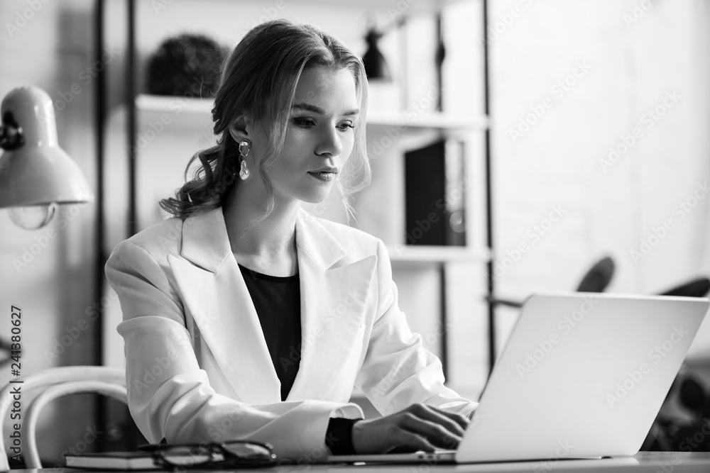 Fototapeta black and white photo of businesswoman in formal wear sitting at desk and typing on laptop at workplace