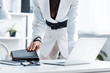 cropped view of businesswoman in formal wear holding notebook at computer desk