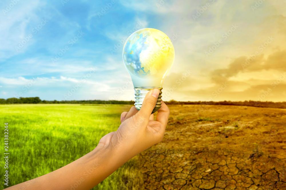 Fototapeta Human hands holding earth inside the light bulb