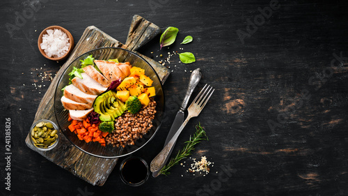 Fotobehang Kip Bowl Buddha. Buckwheat, pumpkin, chicken fillet, avocado, carrots. On a black background. Top view. Free space for your text.