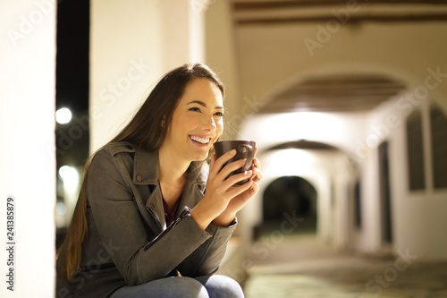 Photo  Happy woman drinking coffee sitting in a town street in the night