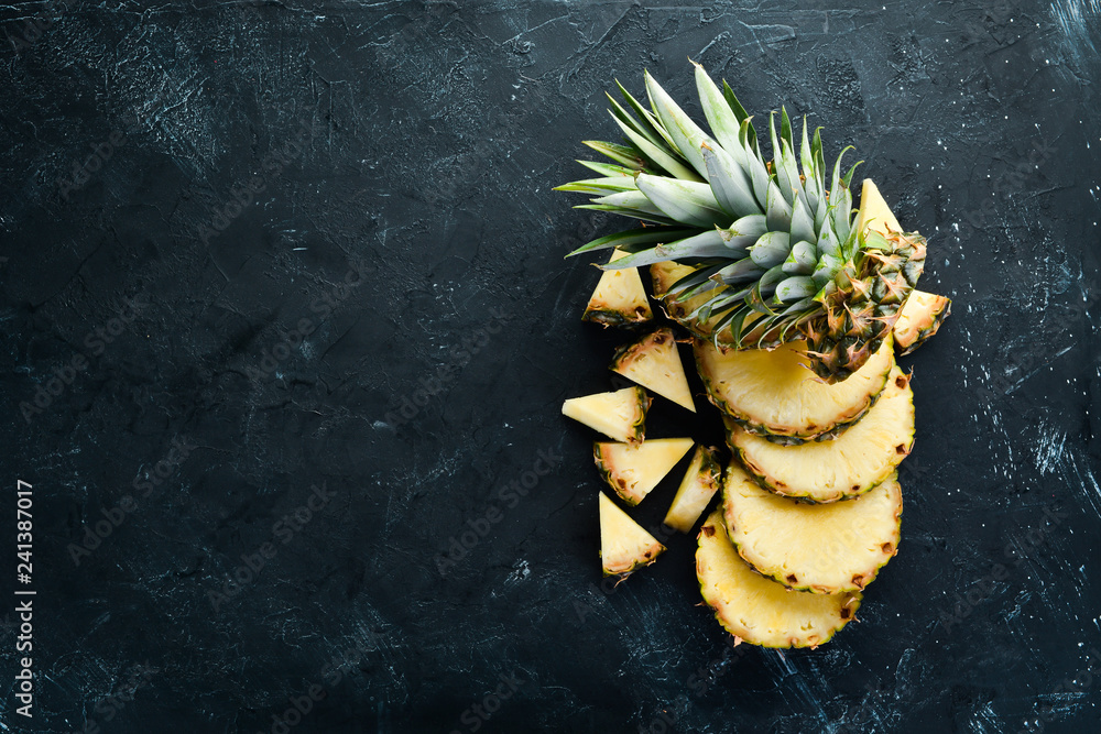 Fototapeta Sliced pineapple on a black background. Tropical Fruits. Top view. Free copy space.