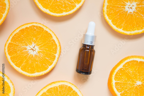 Fototapeta Natural vitamin c serum, skincare, essential oil products. Cosmetic brown glass vial w/ dropper and fresh juicy orange fruit slice on orange background. Beauty product branding mock-up. Top view. obraz