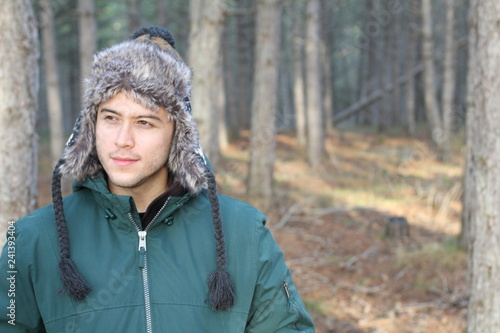 Photo Ethnic man with winter hat in the forest
