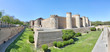 The facade with towers and walls of the Islamic Aljaferia fortress, with lawn and plants in the moat garden, in a sunny summer, in Zaragoza, Spain