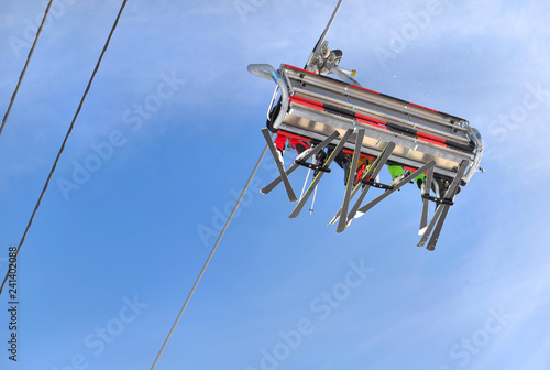 people in ski lift seen from below under blue sky