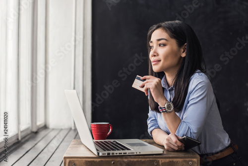 Foto  Young asian woman holding credit card and using laptop computer