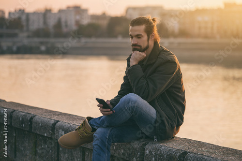 Fototapety, obrazy: Sad businessman holding phone while sitting by the river.