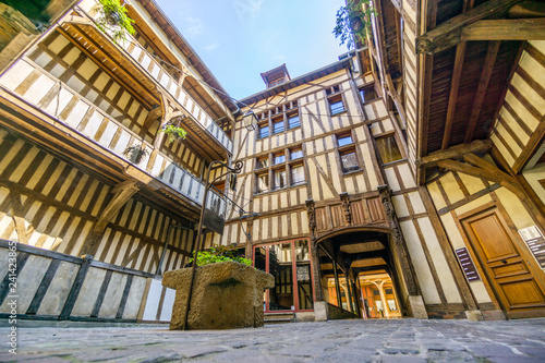 Medieval courtyard surrounded by half timbered houses with well in the middle of Fotobehang