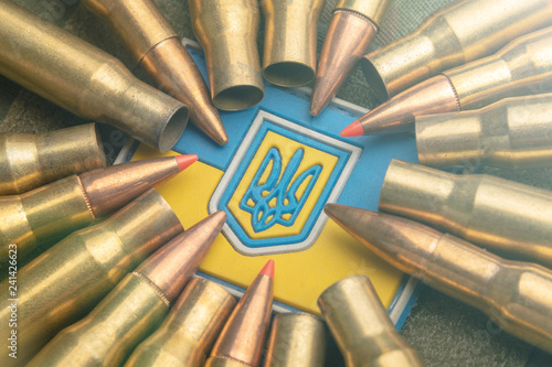 Ukrainian flag on the background of a camouflage military jacket and combat bullets Wallpaper Mural