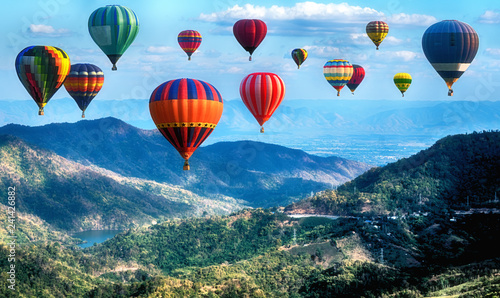 Montgolfière / Dirigeable Hot Air balloons flying over road in forest landscape sunset background.