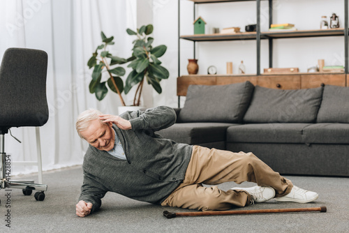 old men falled down on floor and touching head Fototapet