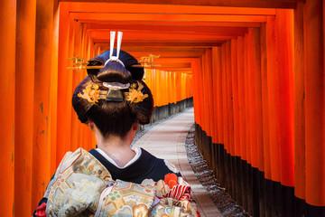 Panel Szklany Japoński Woman in traditional kimono walking at torii gates, Japan