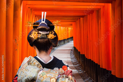 Fototapeta Woman in traditional kimono walking at torii gates, Japan