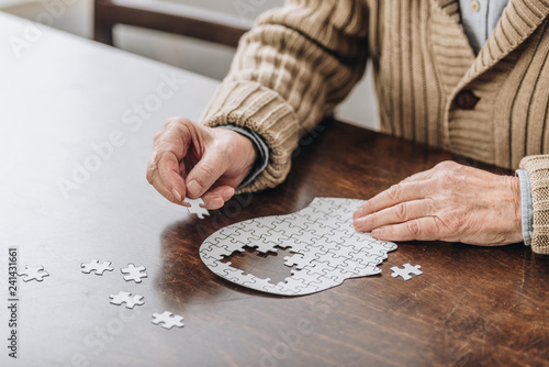 Obraz cropped view of senior man playing with puzzles - fototapety do salonu