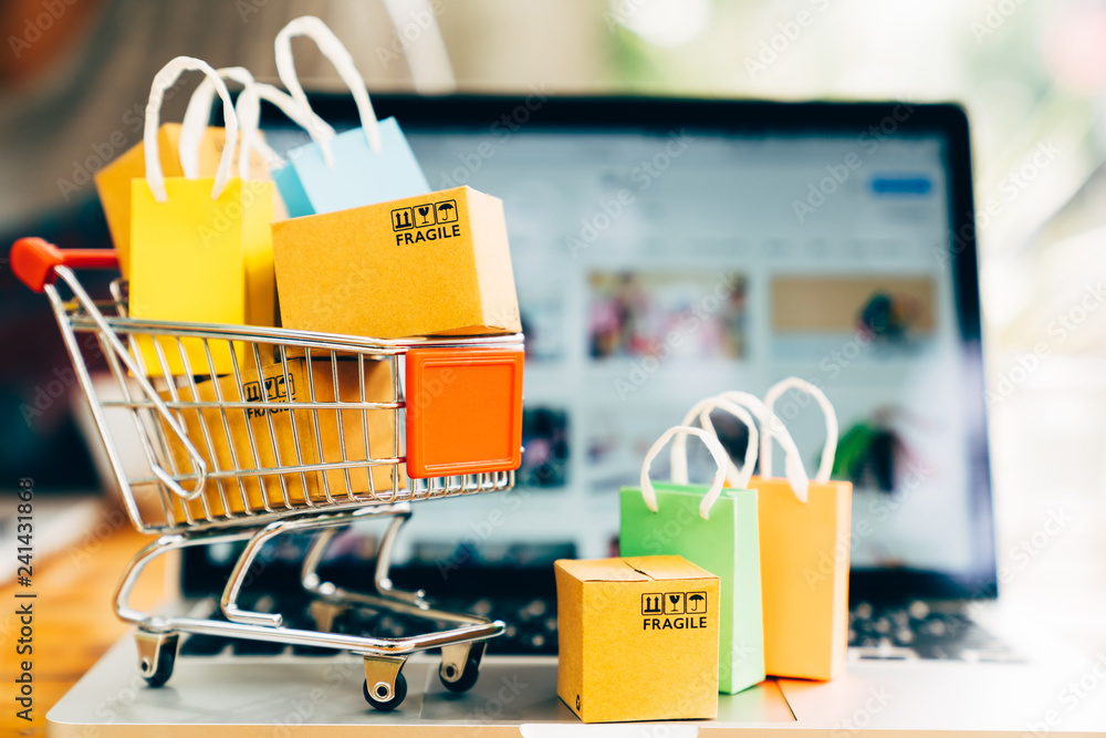 Fototapety, obrazy: Product package boxes and shopping bag in cart with laptop computer which web store shop on screen for online shopping and delivery concept