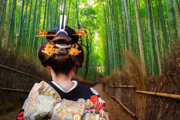 Fototapeta Bambus Woman in traditional kimono walking at bamboo forest of Arashiyama, Japan
