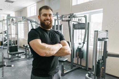 Smiling positive confident male personal instructor with arms crossed in fitness gym