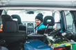 smiling woman sitting in car. snowboard in car trunk. road trip