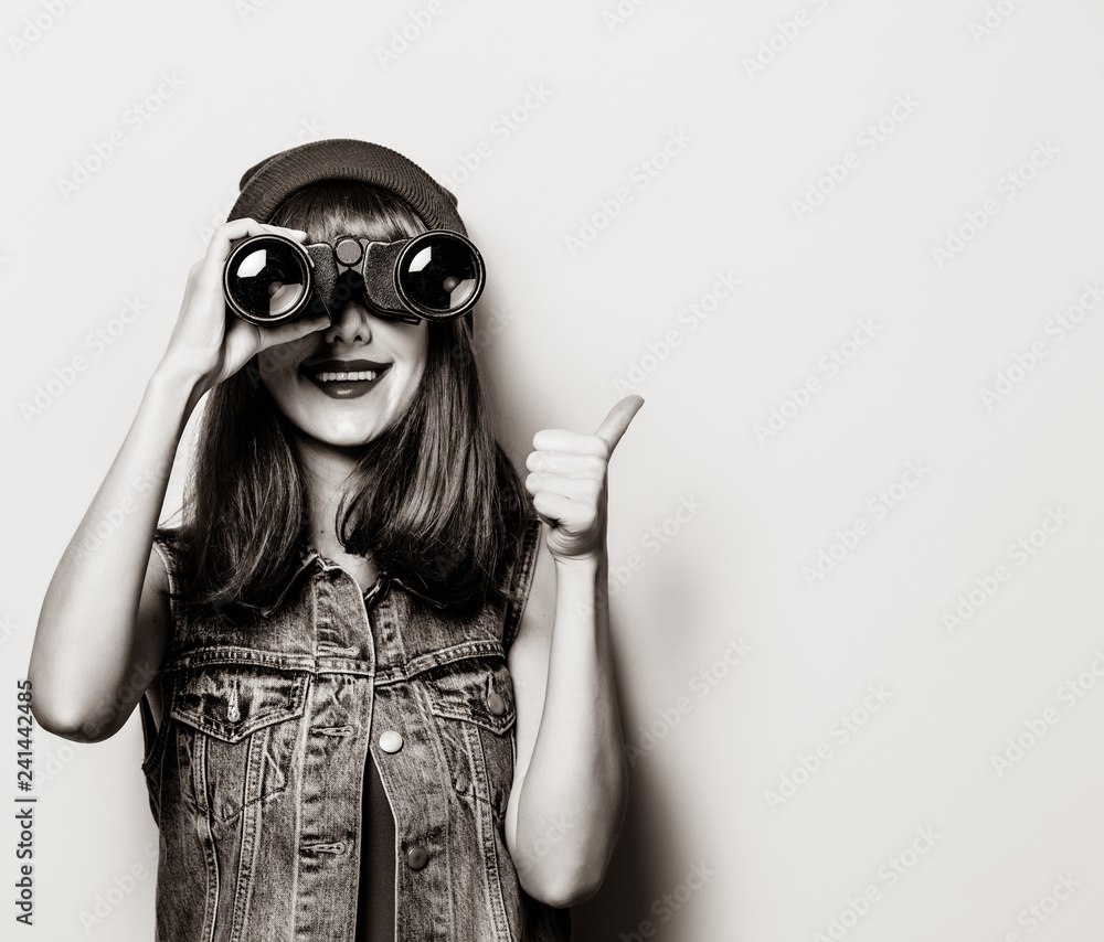 Fototapeta Portrait of young style hipster girl with binoculars . Image in black and white color style