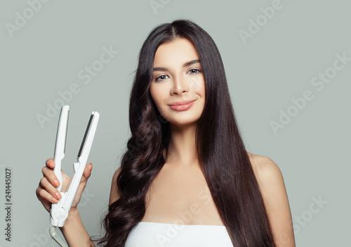 Fényképezés  Happy woman with straight hair and curly hair using hair straightener