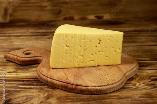 Piece of cheese on cutting board on wooden table