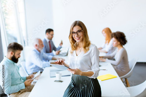 Photographie  Elegant businesswoman standing in office with digital tablet