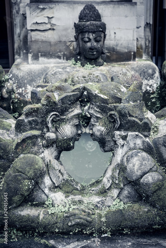 Traditional balinese stone sculpture of a man and woman with moss