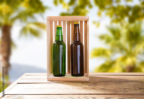 Foto op Canvas Bier / Cider beer bottles on wooden table on a blurred tropical background