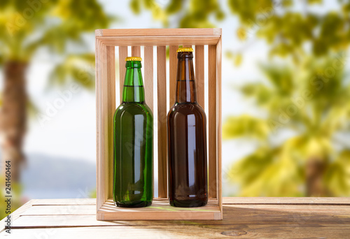 Foto op Canvas Bier / Cider green and grey beer bottles on table on blurred tropical background