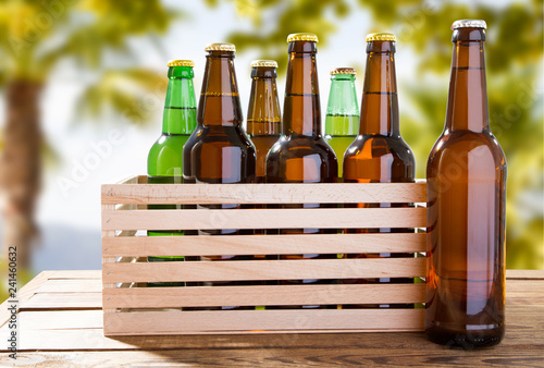 Foto op Canvas Bier / Cider craft beer bottles on wooden table on blurred tropical background