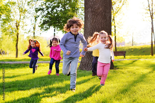 Fotografie, Obraz  a group of small happy children run through the park in the background of grass and trees