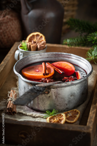 Hot and sweet mulled red wine with cinnamon and oranges