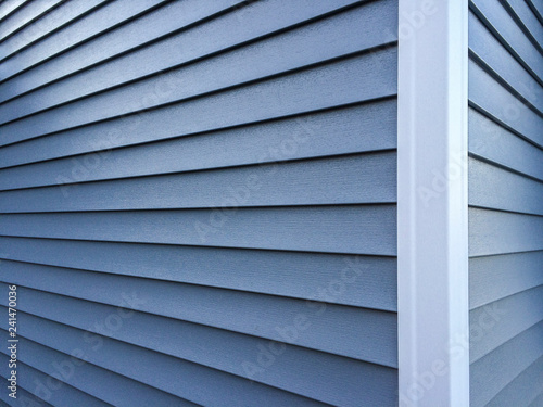 Valokuva  Blue vinyl siding with white trim on the outside wall of a new home