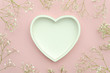 Leinwanddruck Bild - Flat lay. Frame shaped wooden heart with copy space for your text and flowering plants on pink background. Saint Valentines concept.