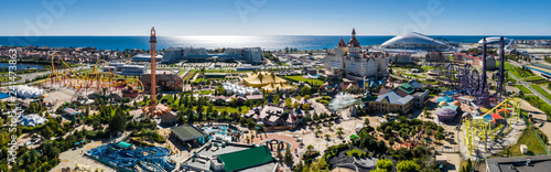 Poster Attraction parc RUSSIA, SOCHI - JUL 27, 2018: Amusement park near hotel Bogatyr at summer sunny day. Aerial view. Photo with noise from action camera