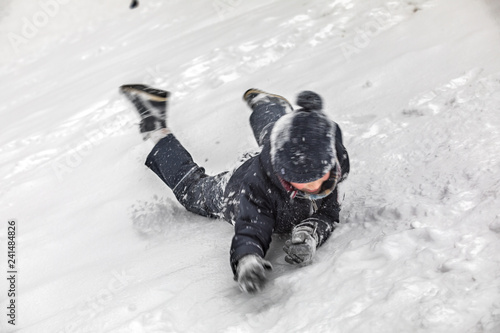 The boy in winter warm clothes slides head over heels from the snow high mountain lying. Snow splashes from under it. Long endurance, motion blur