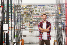 Man Standing Near Showcase With Fishing Equipment In Sports Shop. Space For Text