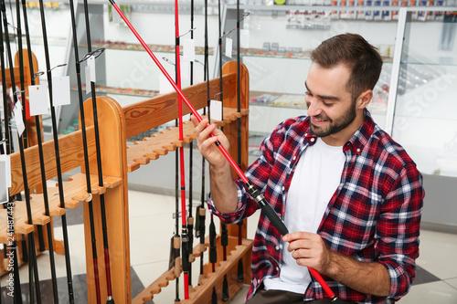 Man choosing fishing rod in sports shop