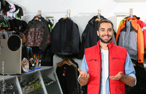 Salesman standing near hangers with fishing clothing in sports shop. Space for text