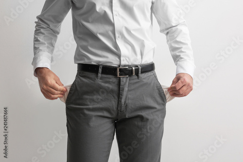 Fotografía  Businessman showing empty pockets on light background, closeup