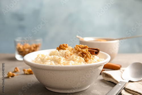 Creamy rice pudding with cinnamon and walnuts in bowl served on table. Space for text