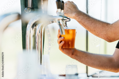 Foto op Canvas Bier / Cider Man serving draft beer in a disposable cup