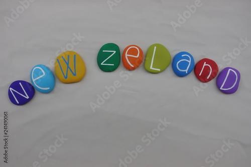 Fotografia  New Zeland, souvenir with multi colored stones over white sand