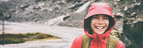 Leinwand Poster Active outdoors people lifestyle - happy hiker Asian woman laughing in the rain on mountain hike - Outdoors adventure trek activity, wearing waterproof raincoat sportswear clothes