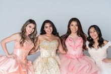 Four Hispanic Girls In Quinceanera Dresses