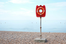A Red Color Lifesaver Buoy On A Beach.